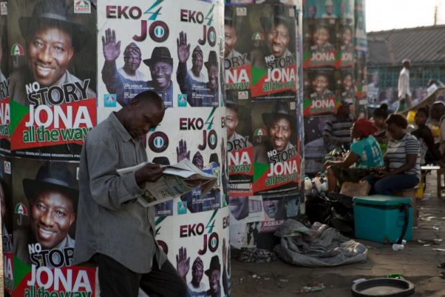 A man reads a newspaper in front of electoral campaign posters in Lagos