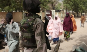 """In this photo taken Wednesday, April 8, 2015, civilians walk past  a  check point manned by Nigerian soldiers in Gwoza, Nigeria, a town newly liberated from Boko Haram.   Each day brings new reports of atrocities, with mass graves being discovered in towns seized back from the militants who had set up a so-called """"Islamic caliphate"""" across a great swath of northeast Nigeria. Boko Haram's nearly 6-year-old Islamic uprising in northeast Nigeria that has killed thousands — a reported 10,000 just last year — and forced more than 1.5 million from their homes.  (AP Photo/Lekan Oyekanmi)"""